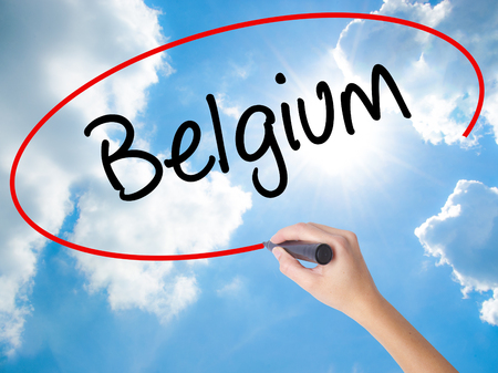 Woman Hand Writing Belgium  with black marker on visual screen. Isolated on Sunny Sky. Business concept. Stock Photo Stock Photo