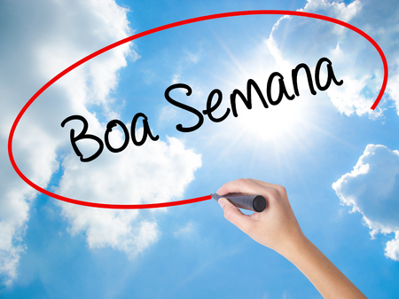 Woman Hand Writing Boa semana   (Good WeekIn portuguese)with black marker on visual screen. Isolated on Sunny Sky. Business concept. Stock Photo
