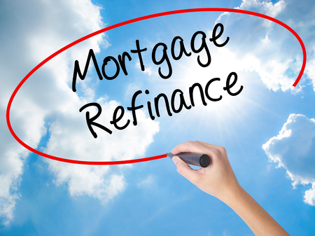 Woman Hand Writing Mortgage Refinance with black marker on visual screen. Isolated on Sunny Sky. Business concept. Stock Photo Stock Photo