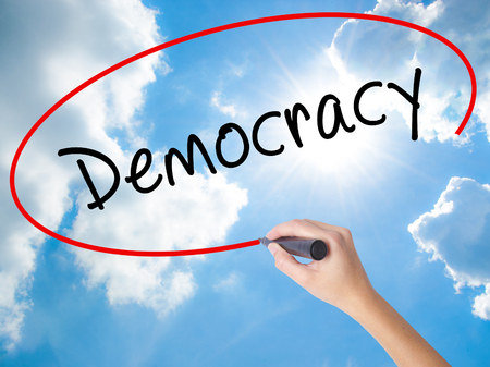Woman Hand Writing Democracy with black marker on visual screen. Isolated on Sunny Sky. Business concept. Stock Photo Stock Photo