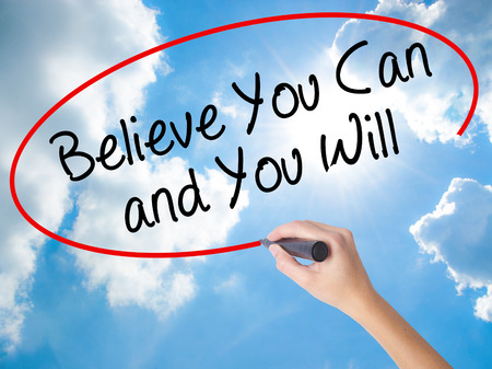 Woman Hand Writing Believe You Can and You Will with black marker on visual screen. Isolated on Sunny Sky. Business concept. Stock Photo Stock fotó