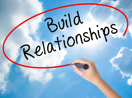 Woman Hand Writing Build Relationships with black marker on visual screen. Isolated on Sunny Sky. Business concept. Stock Photo Stock Photo