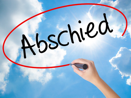 Woman Hand Writing Abschied (Farewell in German) with black marker on visual screen. Isolated on Sunny Sky. Business concept. Stock Photo Stock Photo