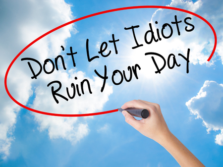 stupidity: Woman Hand Writing Dont Let Idiots Ruin Your Day with black marker on visual screen. Isolated on Sunny Sky. Business concept. Stock Photo