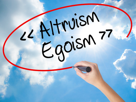 altruism: Woman Hand Writing Altruism - Egoism with black marker on visual screen. Isolated on Sunny Sky. Business concept. Stock Photo Foto de archivo