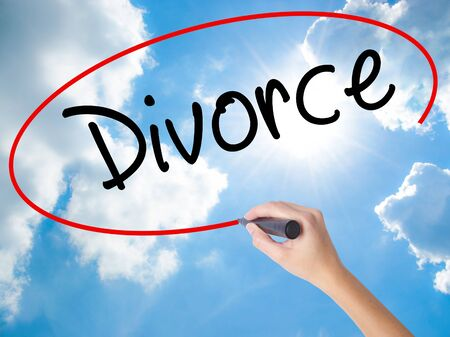Woman Hand Writing Divorce  with black marker on visual screen. Isolated on Sunny Sky. Business concept. Stock Photo