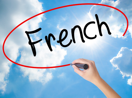 Woman Hand Writing French with black marker on visual screen. Isolated on Sunny Sky. Business concept. Stock Photo