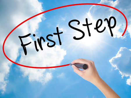 Woman Hand Writing First Step  with black marker on visual screen. Isolated on Sunny Sky. Business concept. Stock Photo