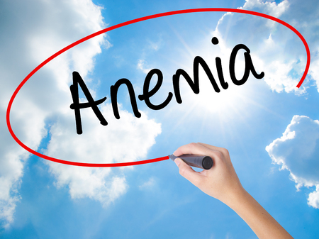 decreased: Woman Hand Writing Anemia  with black marker on visual screen. Isolated on Sunny Sky. Business concept. Stock Photo
