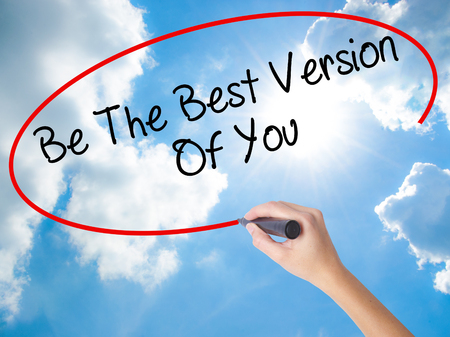 Woman Hand Writing Be The Best Version Of You with black marker on visual screen. Isolated on Sunny Sky. Business concept. Stock Photo Imagens