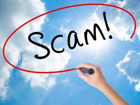 technology transaction: Woman Hand Writing  Scam! with black marker on visual screen. Isolated on Sunny Sky. Business concept. Stock Photo