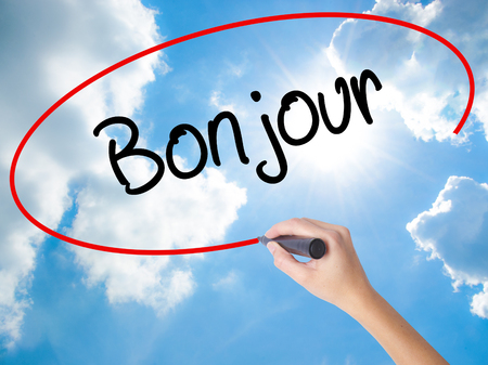 Woman Hand Writing Bonjour  (Good Morning in French) with black marker on visual screen. Isolated on Sunny Sky. Business concept. Stock Photo Stock Photo