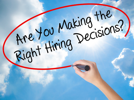 Woman Hand Writing Are You Making the Right Hiring Decisions? with black marker on visual screen. Isolated on Sunny Sky. Business concept. Stock Photo