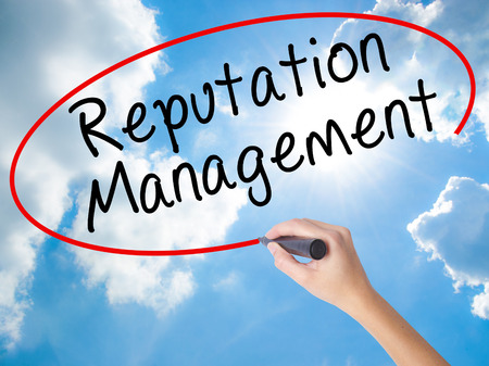 Woman Hand Writing Reputation Management with black marker on visual screen. Isolated on Sunny Sky. Business concept. Stock Photo Stock Photo