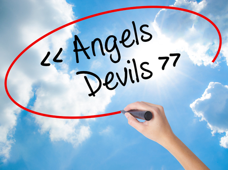 good heavens: Woman Hand Writing Angels - Devils with black marker on visual screen. Isolated on Sunny Sky. Business concept. Stock Photo