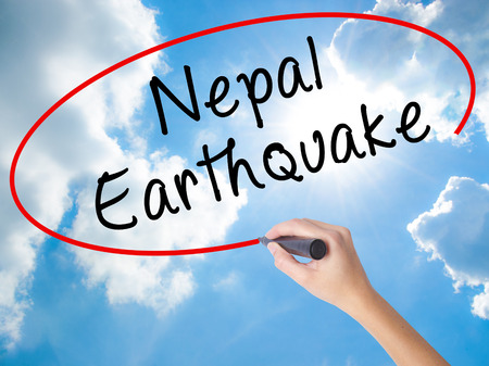 Woman Hand Writing Nepal Earthquake with black marker on visual screen. Isolated on Sunny Sky. Business concept. Stock Photo