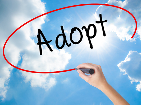 Woman Hand Writing Adopt  with black marker on visual screen. Isolated on Sunny Sky. Business concept. Stock Photo