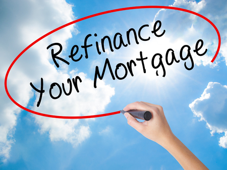 Woman Hand Writing Refinance Your Mortgage with black marker on visual screen. Isolated on Sunny Sky. Business concept. Stock Photo