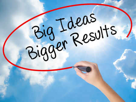 bigger: Woman Hand Writing Big Ideas Bigger Results  with black marker on visual screen. Isolated on Sunny Sky. Business concept. Stock Photo Stock Photo