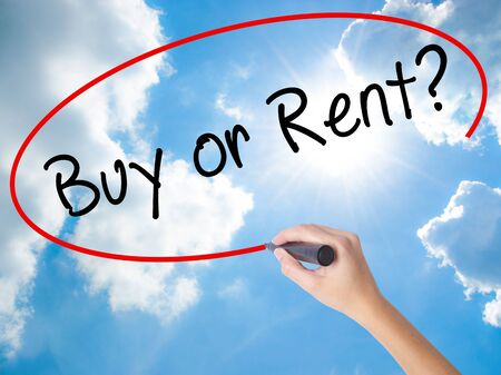 buying questions: Woman Hand Writing Buy or Rent? with black marker on visual screen. Isolated on Sunny Sky. Business concept. Stock Photo