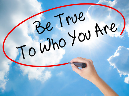 true self: Woman Hand Writing Be True To Who You Are with black marker on visual screen. Isolated on Sunny Sky. Business concept. Stock Photo