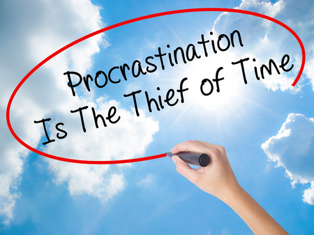 Woman Hand Writing  Procrastination Is The Thief of Time with black marker on visual screen. Isolated on Sunny Sky. Business concept. Stock Photo