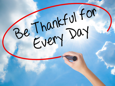 Woman Hand Writing Be Thankful for Every Day   with black marker on visual screen. Isolated on Sunny Sky. Business concept. Stock Photo
