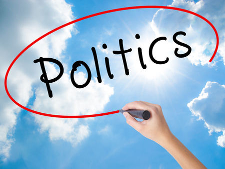Woman Hand Writing Politics with black marker on visual screen. Isolated on Sunny Sky. Business concept. Stock Photo