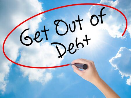 Woman Hand Writing Get Out of Debt with black marker on visual screen. Isolated on Sunny Sky. Business concept. Stock Photo