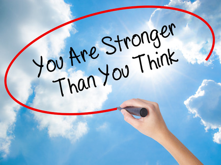 Woman Hand Writing You Are Stronger Than You Think with black marker on visual screen. Isolated on Sunny Sky. Business concept. Stock Photo Stock Photo