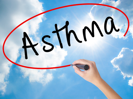 Woman Hand Writing Asthma with black marker on visual screen. Isolated on Sunny Sky. Business concept. Stock Photo