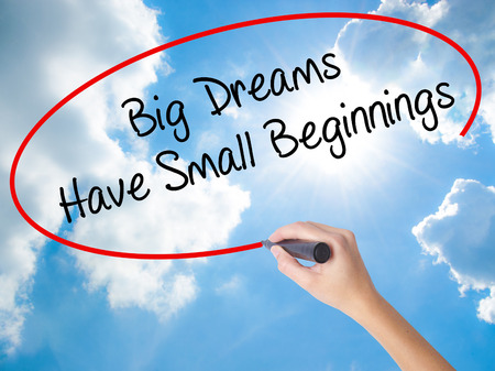 Woman Hand Writing Big Dreams Have Small Beginnings with black marker on visual screen. Isolated on Sunny Sky. Business concept. Stock Photo