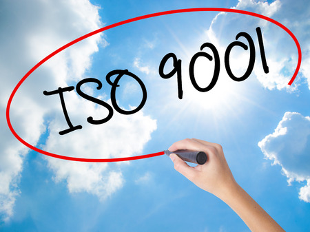 Woman Hand Writing  Iso 9001 with black marker on visual screen. Isolated on Sunny Sky. Business concept. Stock Photo Stock Photo