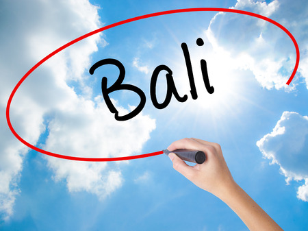 bali province: Woman Hand Writing Bali  with black marker on visual screen. Isolated on Sunny Sky. Business concept. Stock Photo