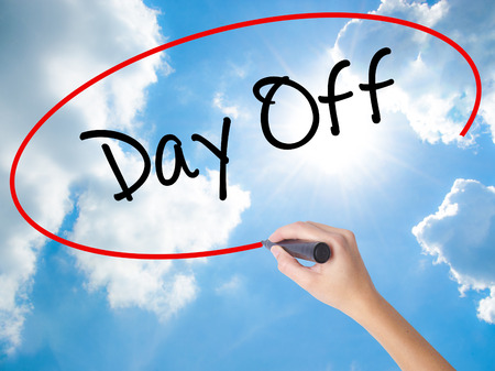 Woman Hand Writing Day Off  with black marker on visual screen. Isolated on Sunny Sky. Business concept. Stock Photo