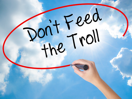 Woman Hand Writing Dont Feed the Troll with black marker on visual screen. Isolated on Sunny Sky. Business concept. Stock Photo Stock Photo