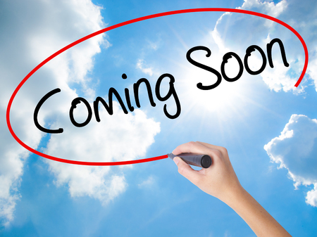 Woman Hand Writing Coming Soon with black marker on visual screen. Isolated on Sunny Sky. Business concept. Stock Photo