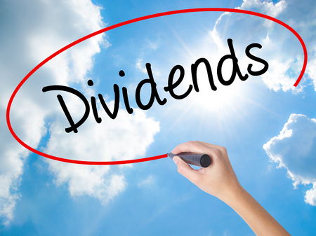 Woman Hand Writing Dividends with black marker on visual screen. Isolated on Sunny Sky. Business concept. Stock Photo