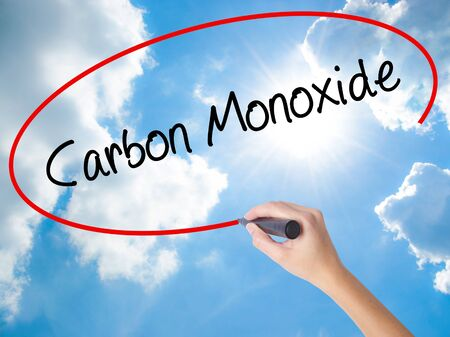 Woman Hand Writing Carbon Monoxide  with black marker on visual screen. Isolated on Sunny Sky. Business concept. Stock Photo