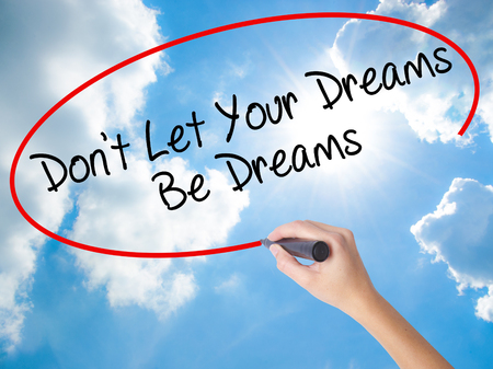 Woman Hand Writing Dont Let Your Dreams Be Dreams with black marker on visual screen. Isolated on Sunny Sky. Business concept. Stock Photo Stock Photo