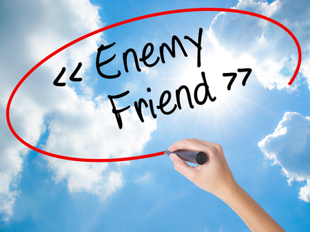duplicitous: Woman Hand Writing Enemy - Friend with black marker on visual screen. Isolated on Sunny Sky. Business concept. Stock Photo Stock Photo