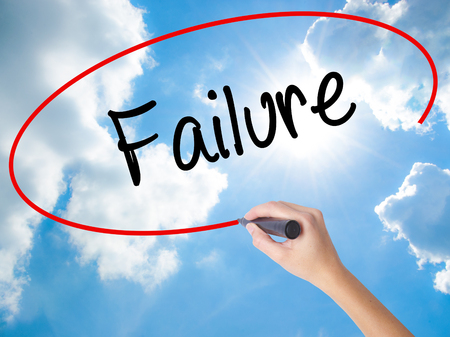 Woman Hand Writing Failure with black marker on visual screen. Isolated on Sunny Sky. Business concept. Stock Photo