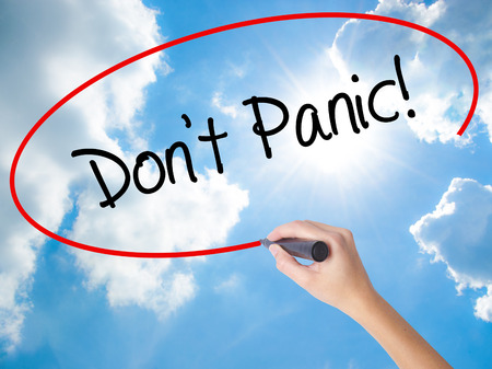 Woman Hand Writing Dont Panic! with black marker on visual screen. Isolated on Sunny Sky. Business concept. Stock Photo Stock Photo