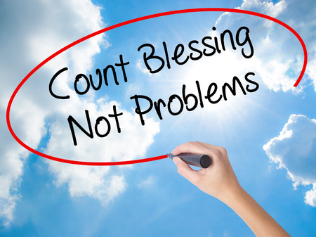 preachment: Woman Hand Writing Count Blessing Not Problems with black marker on visual screen. Isolated on Sunny Sky. Business concept. Stock Photo Stock Photo