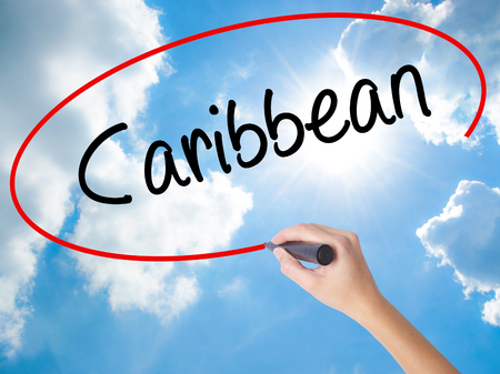 Woman Hand Writing Caribbean with black marker on visual screen. Isolated on Sunny Sky. Business concept. Stock Photo Stock Photo