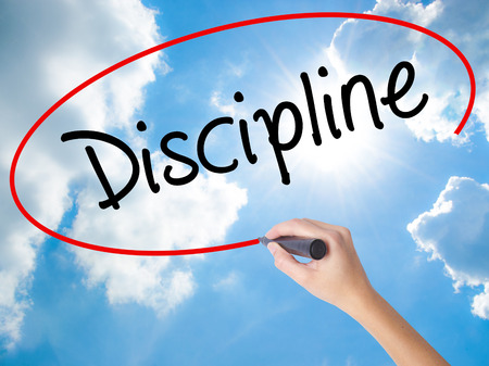 Woman Hand Writing Discipline with black marker on visual screen. Isolated on Sunny Sky. Business concept. Stock Photo