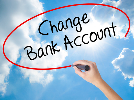Woman Hand Writing Change Bank Account with black marker on visual screen. Isolated on Sunny Sky. Business concept. Stock Photo