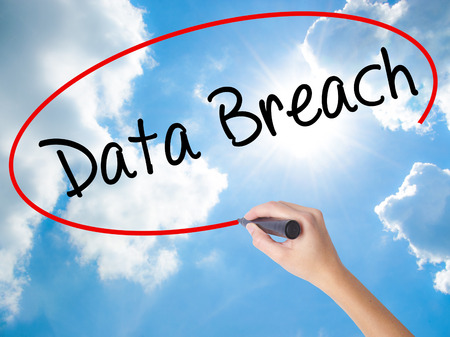 intentional: Woman Hand Writing Data Breach with black marker on visual screen. Isolated on Sunny Sky. Business concept. Stock Photo