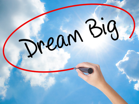 Woman Hand Writing Dream Big  with black marker on visual screen. Isolated on Sunny Sky. Business concept. Stock Photo Stock Photo