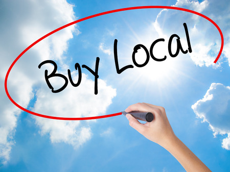 Woman Hand Writing Buy Local  with black marker on visual screen. Isolated on Sunny Sky. Business concept. Stock Photo